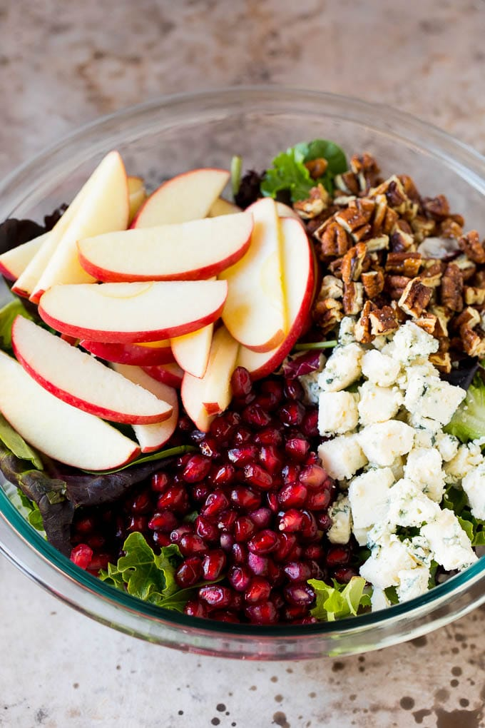 Lettuce topped with apples, blue cheese, pecans and pomegranate seeds.