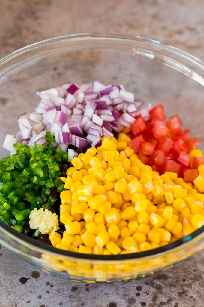 Corn, tomatoes, jalapeno and red onion in a bowl.
