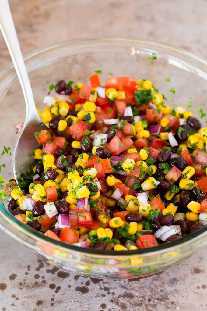Corn, beans, tomatoes and seasonings mixed together in a glass bowl.