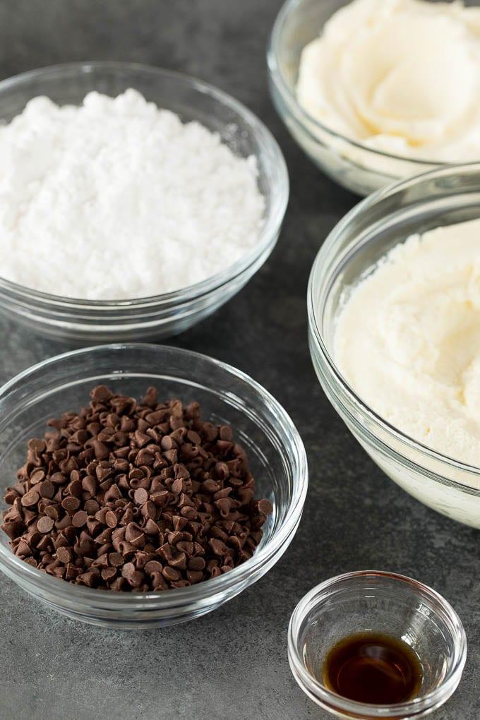 Bowls of mini chocolate chips, ricotta cheese, mascarpone, powdered sugar and vanilla extract.