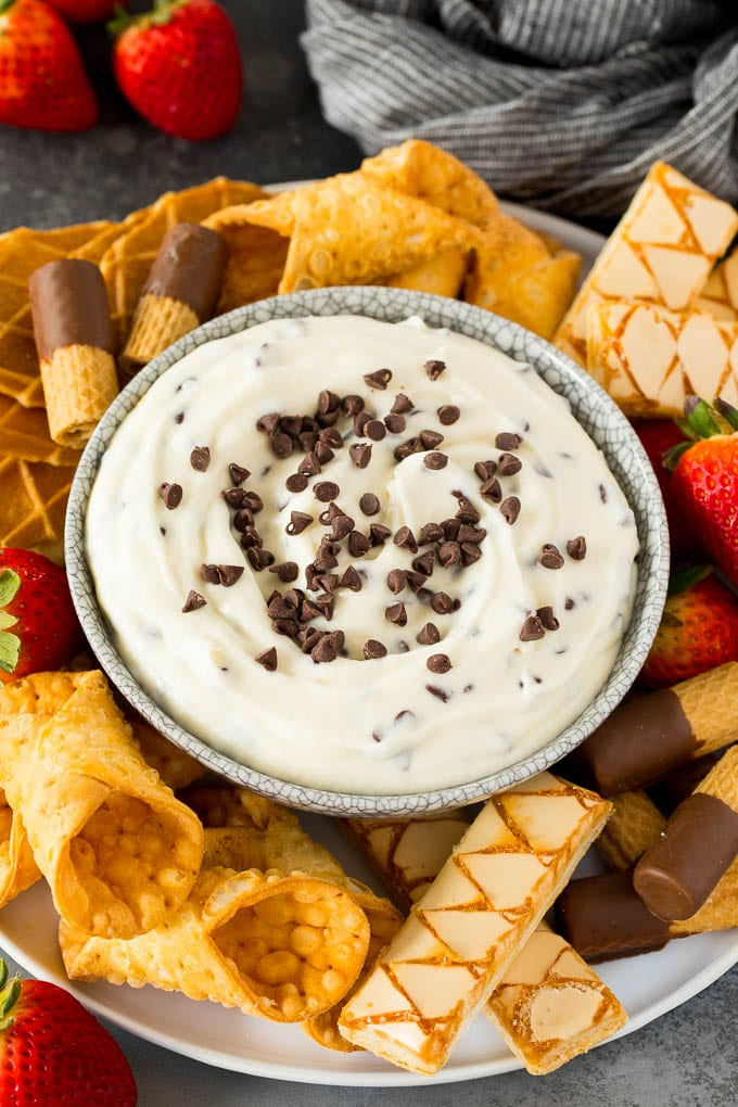 A bowl of cannoli dip surrounded by cookies, cannoli shells and strawberries.