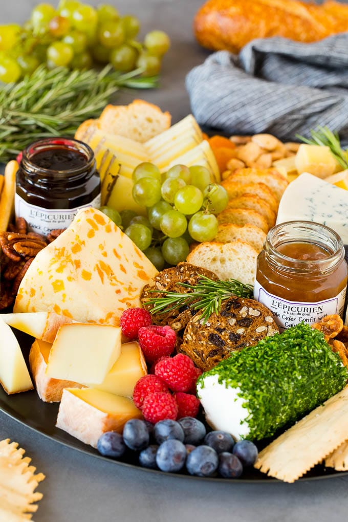 A cheese board with crackers, fruit, nuts and jam.