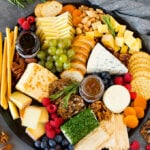 The best cheese board with assorted cheeses, bread, crackers, fruit and nuts.