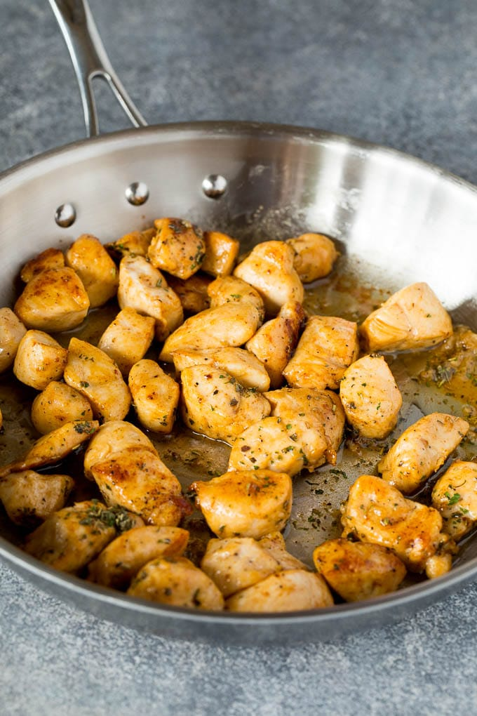 Cooked diced chicken in a skillet.