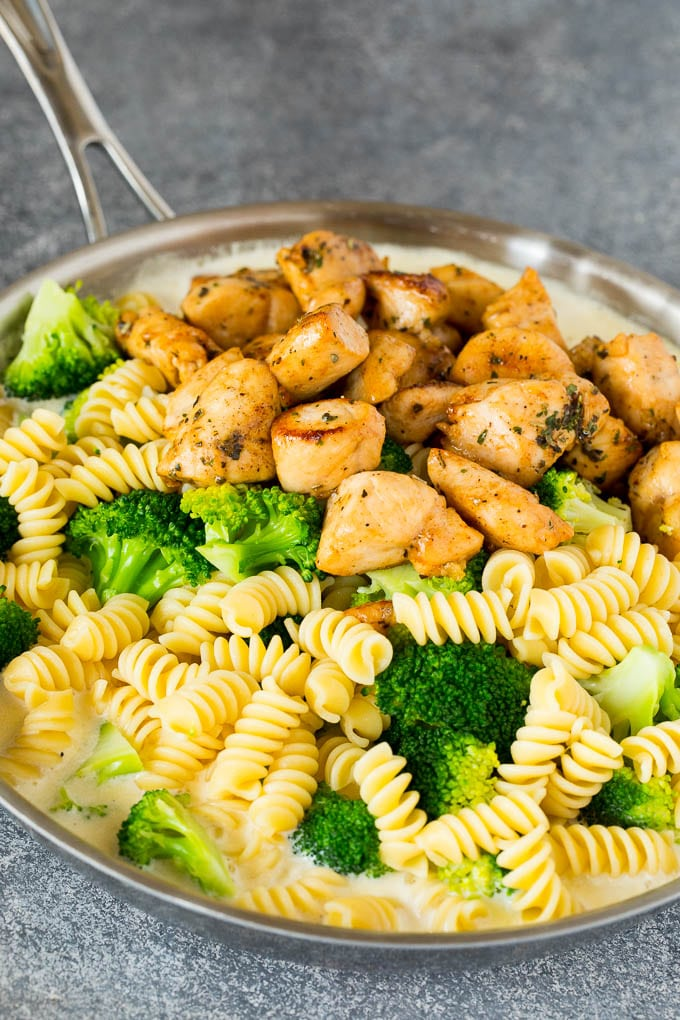 Chicken, pasta and broccoli in a pan of cream sauce.