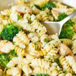 A pan of chicken broccoli Alfredo pasta with a serving spoon in it.
