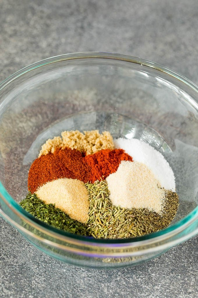 A mixing bowl with salt, pepper, dried herbs and spices.