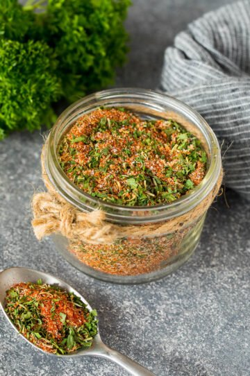 A jar of chicken seasoning made with dried herbs and spices.
