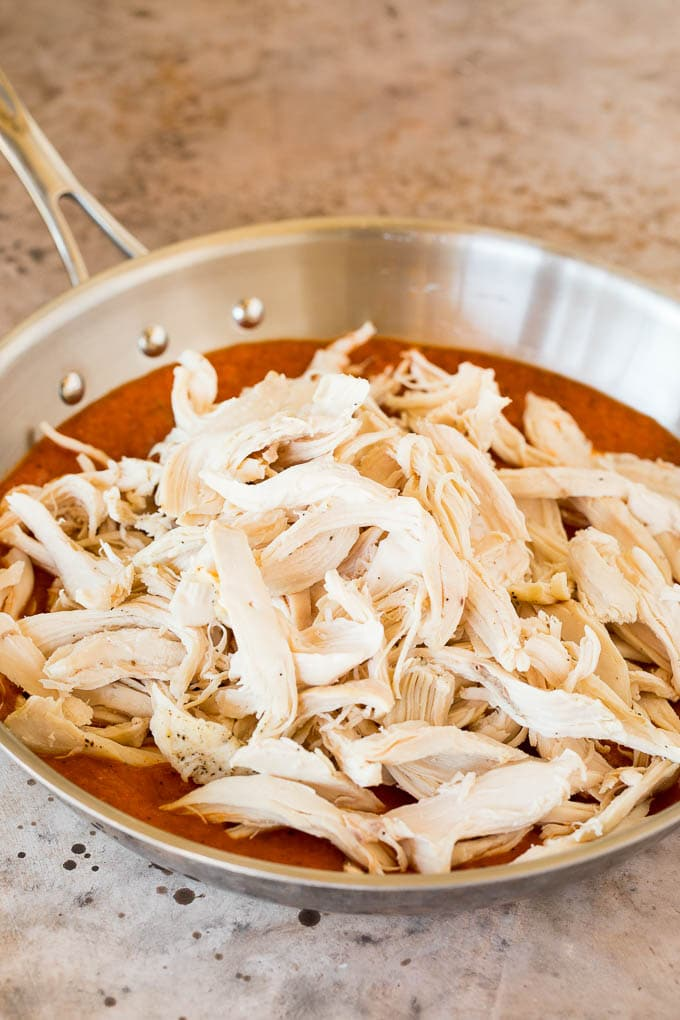 Shredded chicken in a pan of tomato sauce.