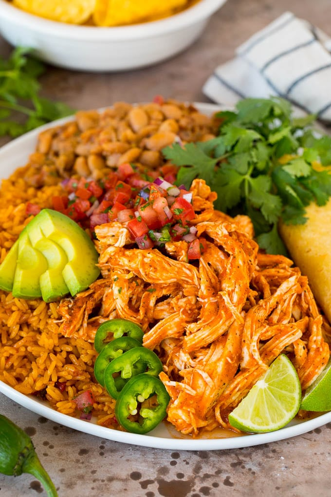 Chicken tinga served with rice, beans, avocado and salsa.