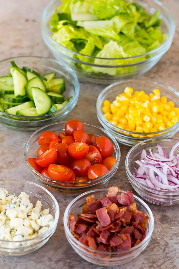 Bowls of lettuce, vegetables, bacon and blue cheese.