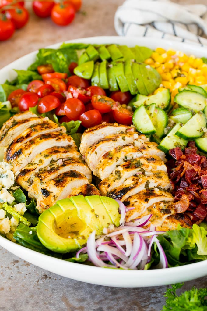 A bowl of grilled chicken salad with tomatoes, avocado and red onion.