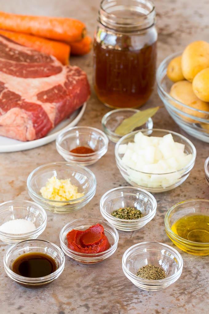 Ingredients including a beef roast, carrots, potatoes and seasonings.
