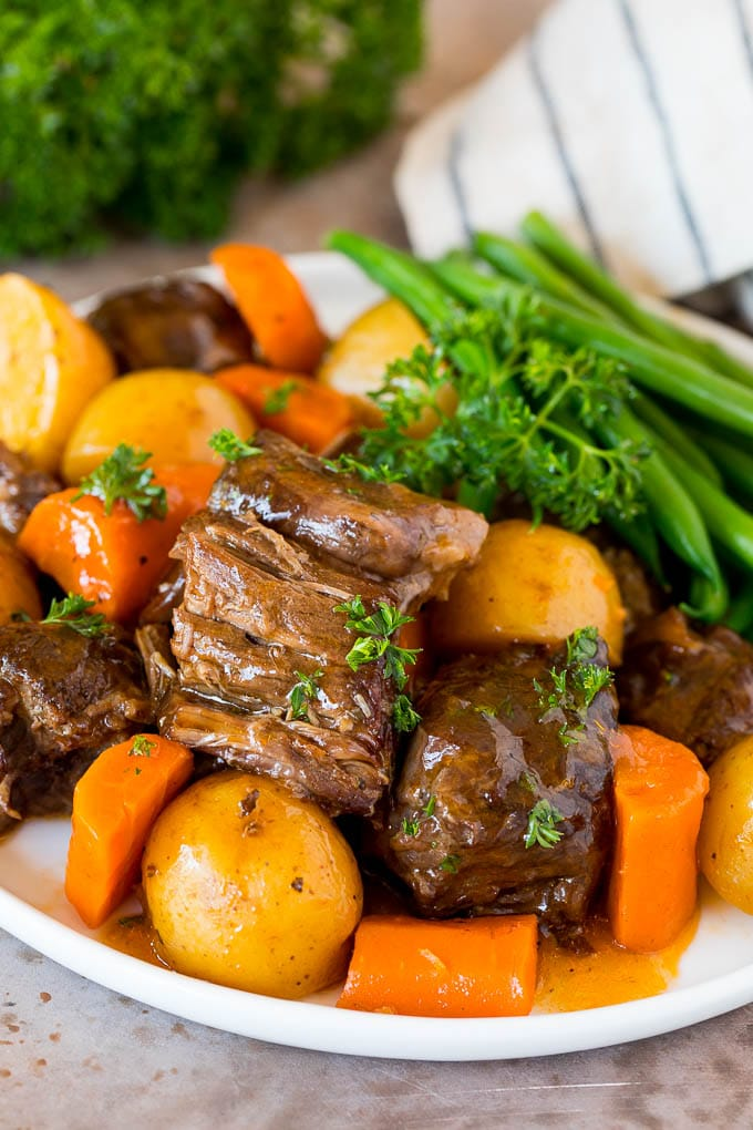 A plate of Instant Pot pot roast served with carrots, green beans and potatoes.