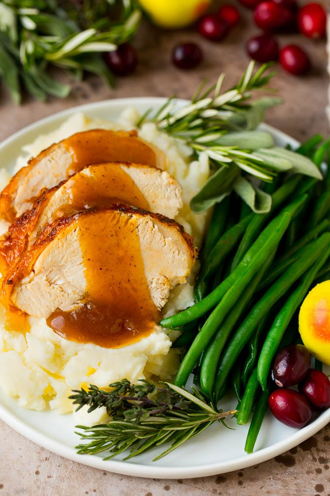 Instant Pot turkey breast sliced and served with mashed potatoes and gravy.