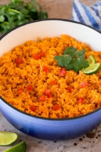 A pot of Mexican rice garnished with tomatoes, cilantro and lime wedges.