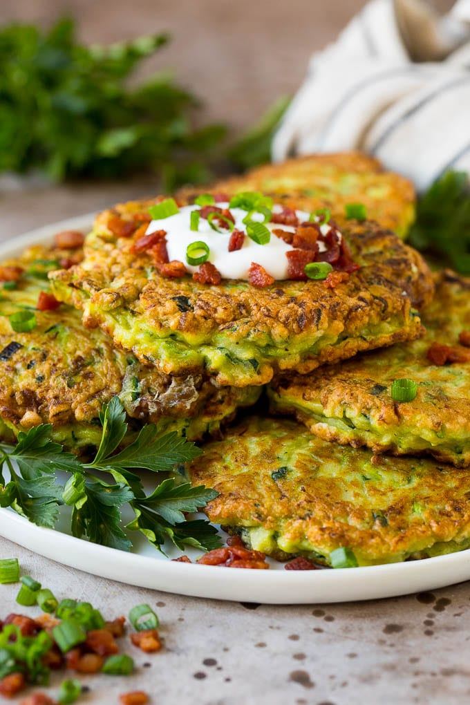 A plate of zucchini fritters garnished with fresh herbs.