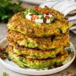 A stack of zucchini fritters topped with sour cream and bacon.
