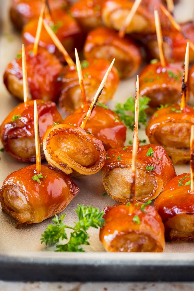 A tray of bacon wrapped water chestnuts garnished with parsley.