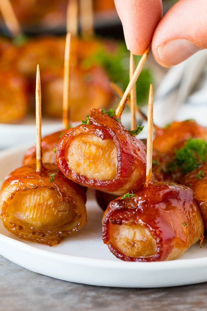 A hand picking up bacon wrapped water chestnuts.
