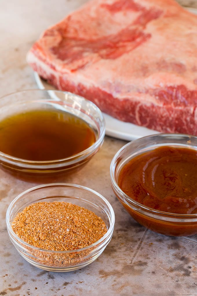 Raw brisket with bowls of beef broth, sauce and seasoning.