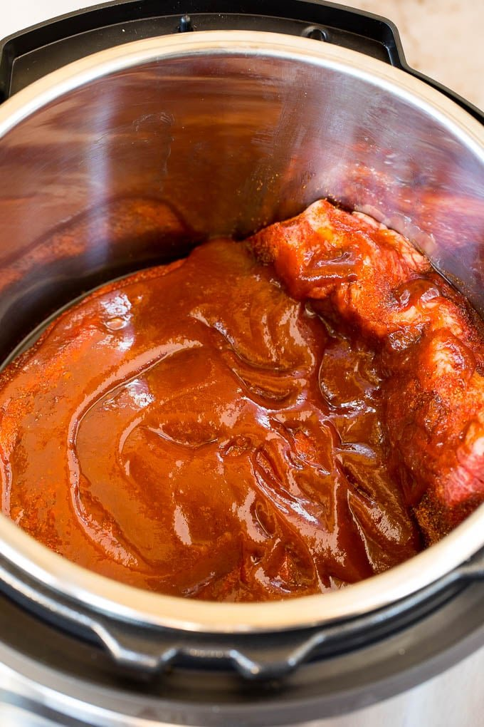 Brisket in a pressure cooker covered in sauce.