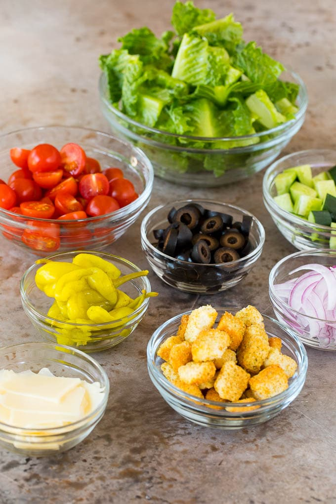 Bowls of lettuce, vegetables, cheese and croutons.
