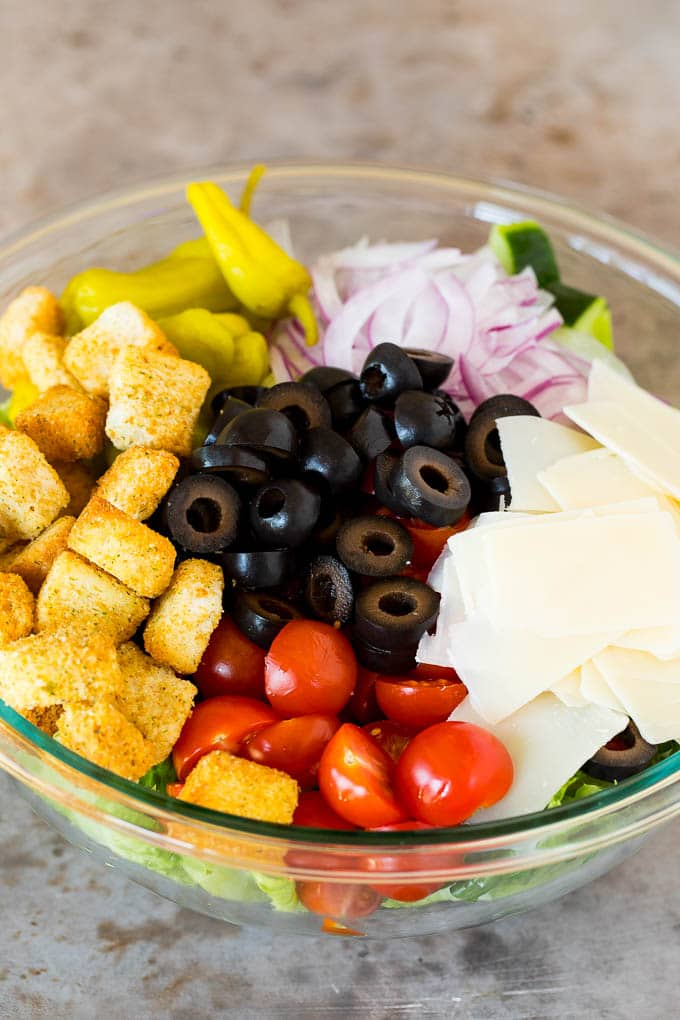 A bowl of lettuce topped with olives, tomatoes, cheese and croutons.