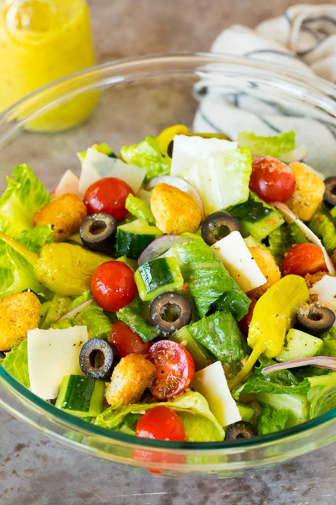 A bowl of Italian salad with cucumber, cheese and croutons.