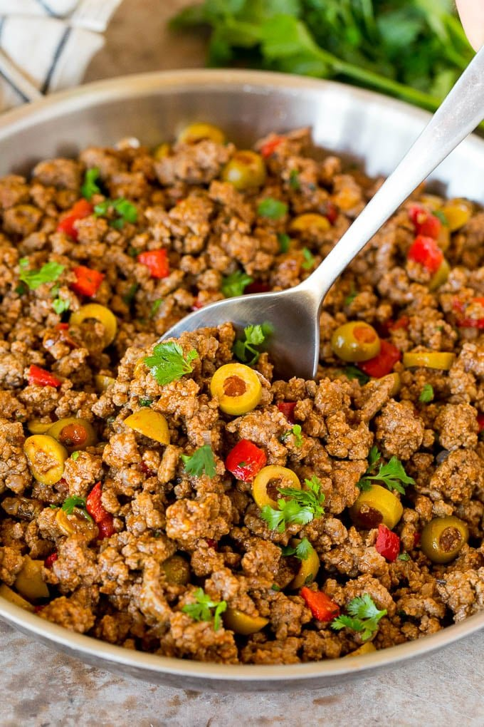 A pan of picadillo with a serving spoon in it.