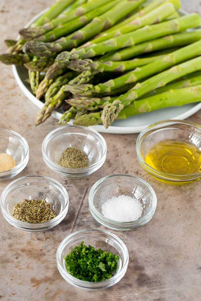 Fresh asparagus with bowls of seasonings and olive oil.
