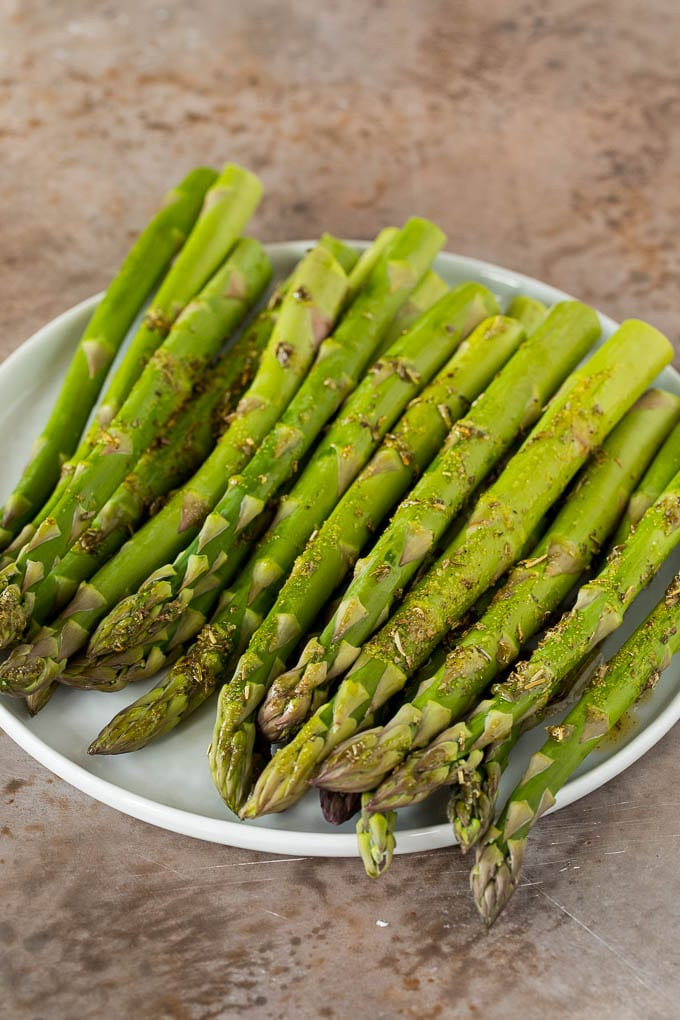 A plate of asparagus stalks coated in seasonings.