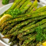 A plate of air fryer asparagus served with parsley and lemon.