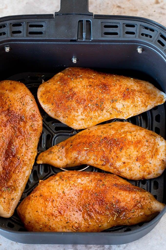 Seasoned chicken breasts inside an air fryer.