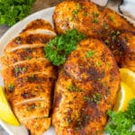 Air fryer chicken breast on a plate with lemon and parsley for garnish.