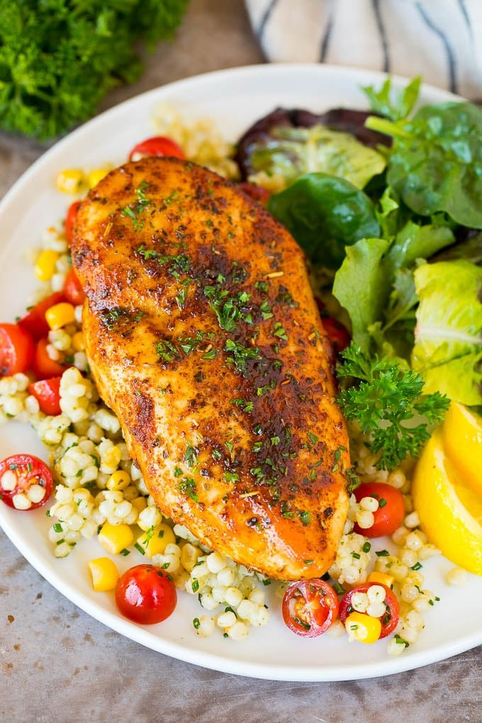 Air fryer chicken breast served with couscous and salad.