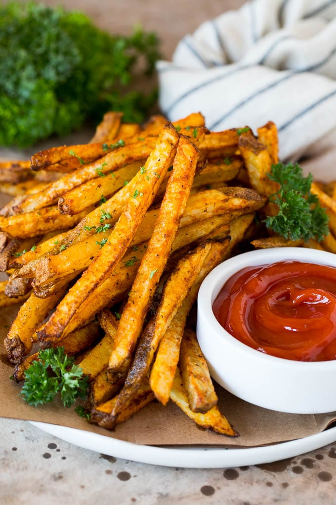 A plate of air fryer french fries garnished with parsley and served with ketchup.