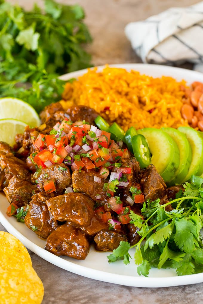 Carne guisada served with rice, beans and avocado.