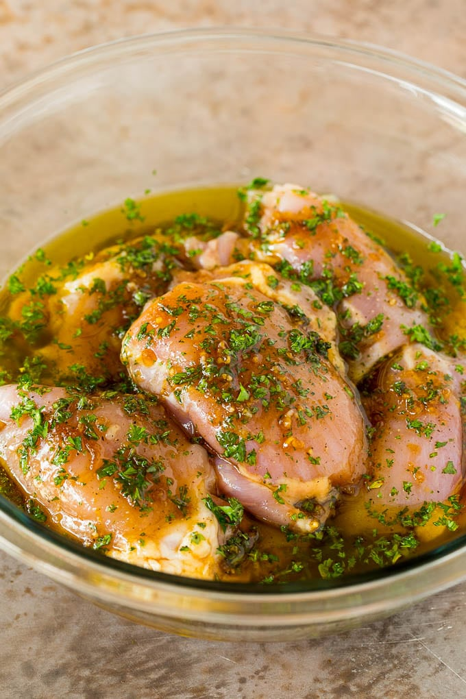 Raw chicken thighs in a bowl of marinade.