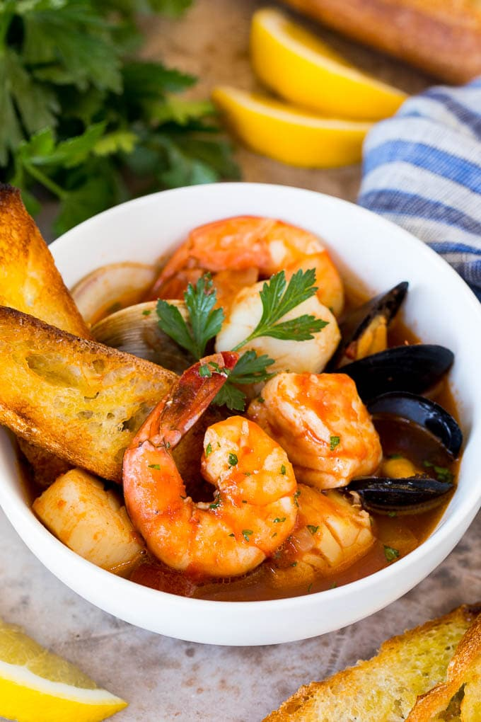A serving bowl of cioppino with grilled bread slices in it.