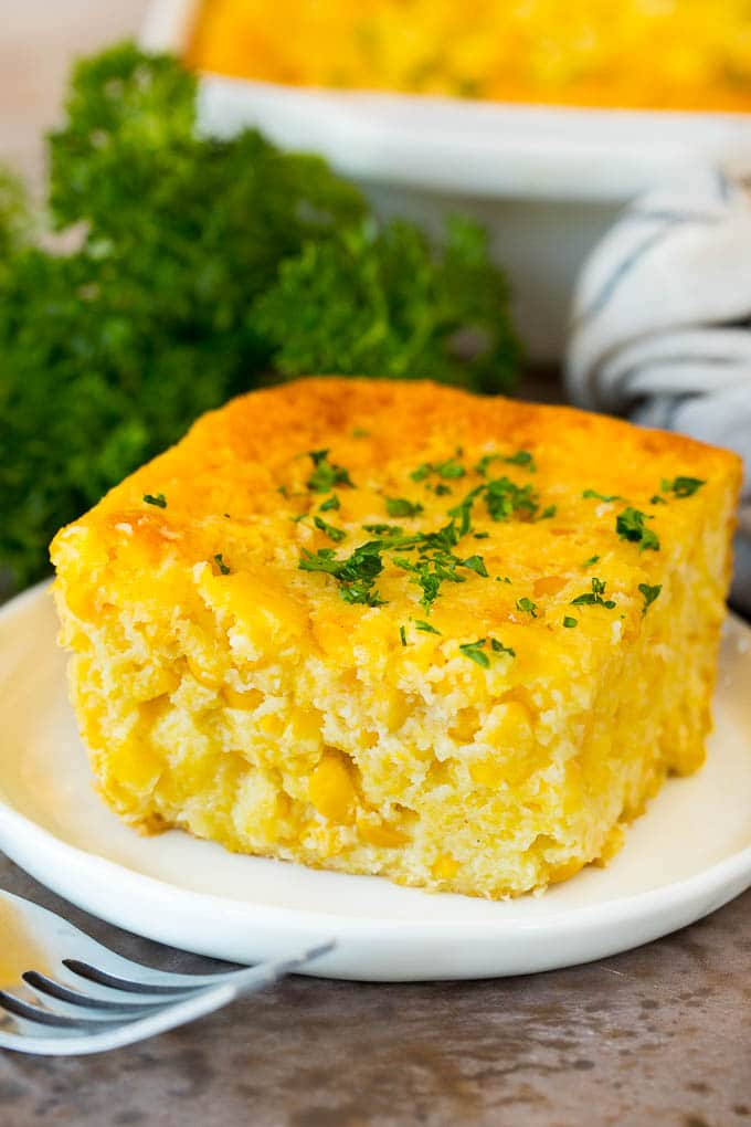 A square of cornbread casserole topped with parsley.