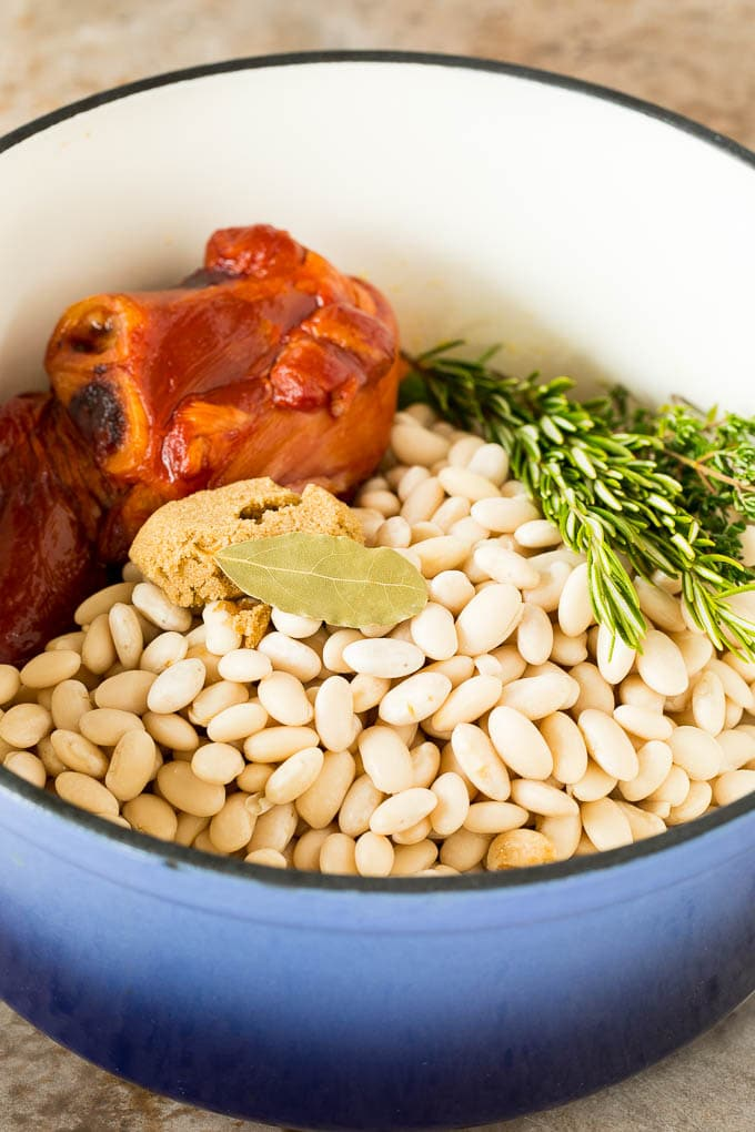 Beans in a pot with a ham hock and herbs.