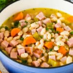 A pot of ham and beans garnished with parsley.