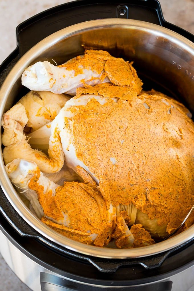 A chicken covered in flavored butter in a pressure cooker.