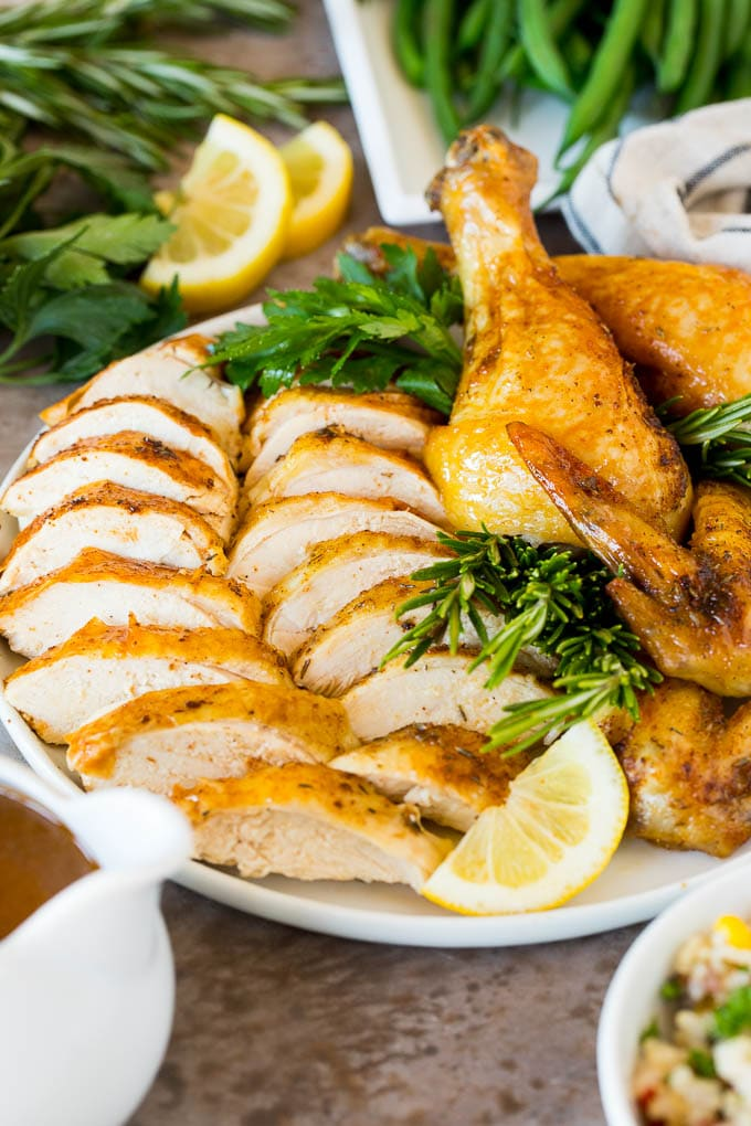 An Instant Pot whole chicken that's been sliced and arranged on a serving plate.
