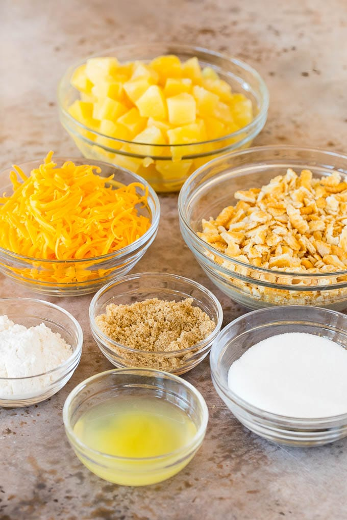 Bowls of pineapple, sugar, crackers and cheese.