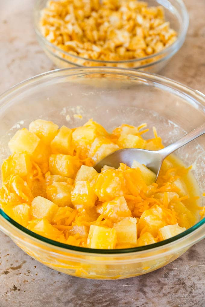 A bowl of pineapple chunks mixed with cheddar cheese, flour and sugar.