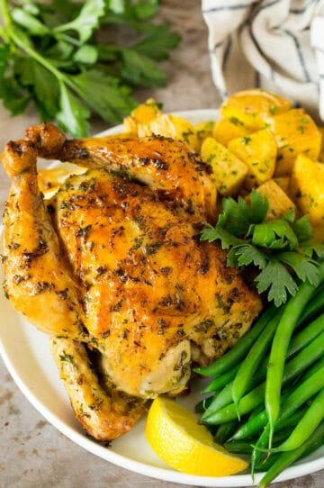 Roasted cornish hen on a plate served with potatoes and green beans.