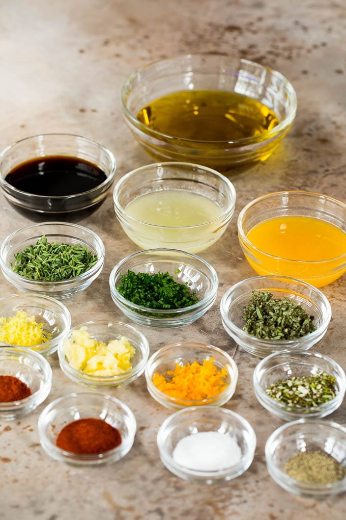Bowls of olive oil, soy sauce, citrus juices, seasonings and herbs.