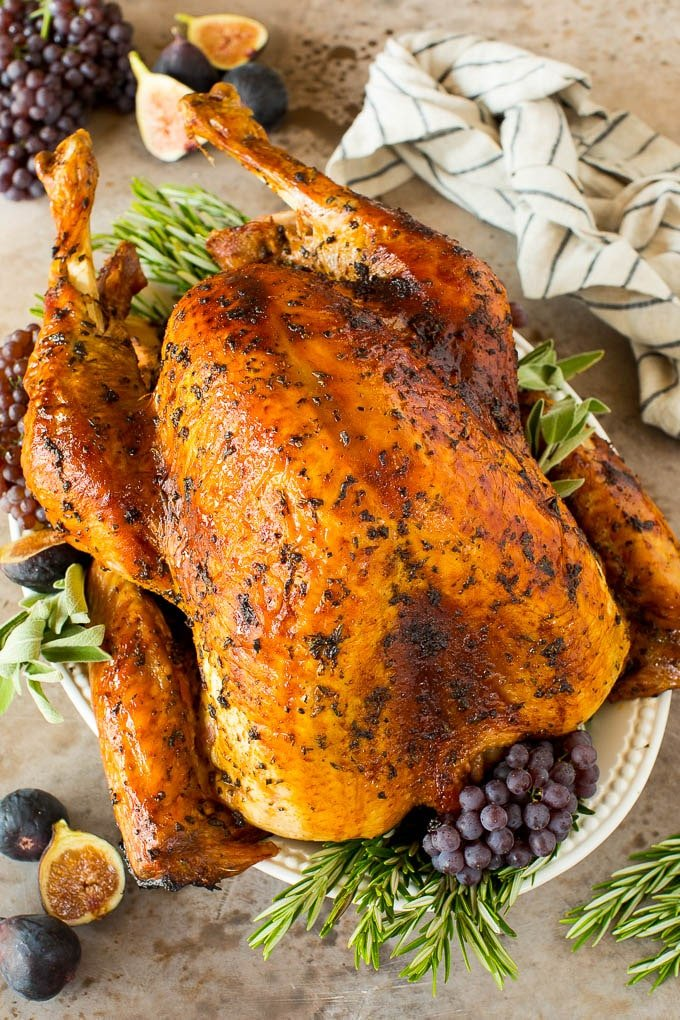 Turkey marinade over a cooked turkey, garnished with herbs and grapes.
